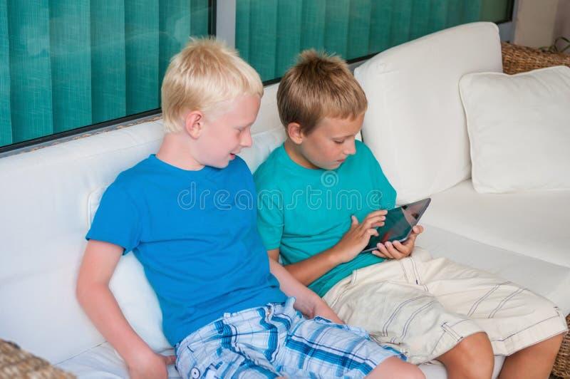 Zwei Jungen, die auf Tablet-Computer des Bildschirm- spielen lizenzfreie stockfotografie