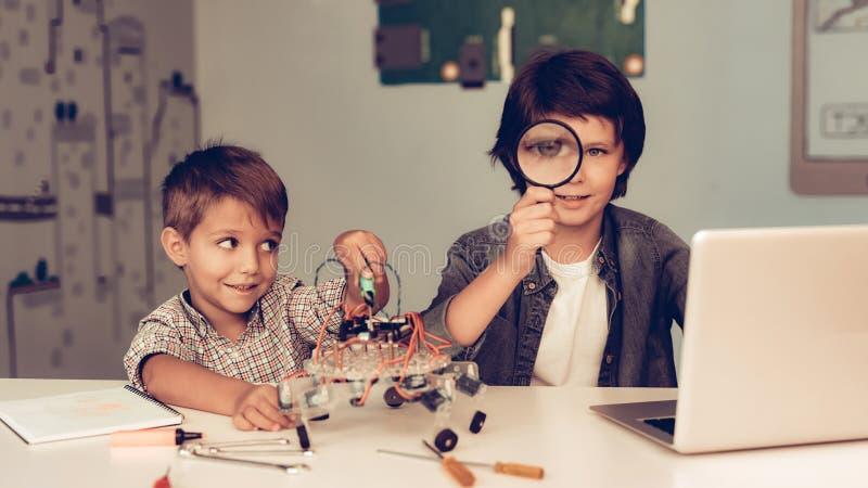 Zwei Jungen, die bei Tisch sitzen und Roboter konstruieren lizenzfreies stockbild