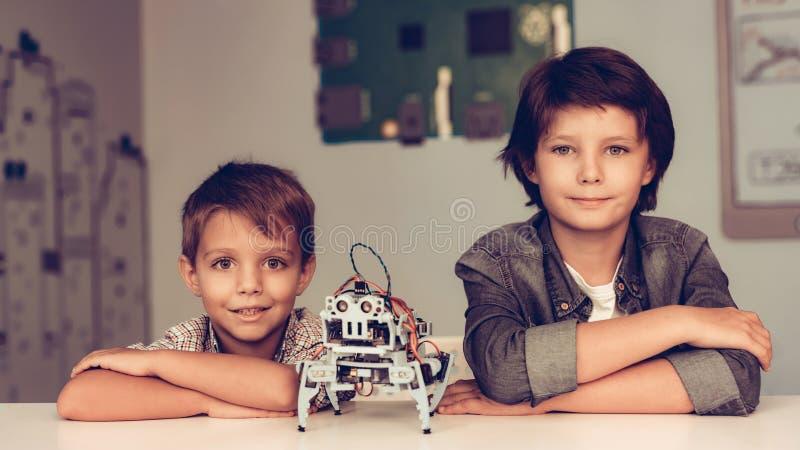 Zwei Jungen, die bei Tisch sitzen und Roboter konstruieren stockbilder