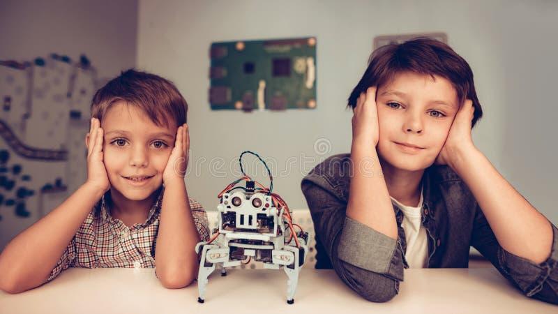 Zwei Jungen, die bei Tisch sitzen und Roboter konstruieren stockfotografie