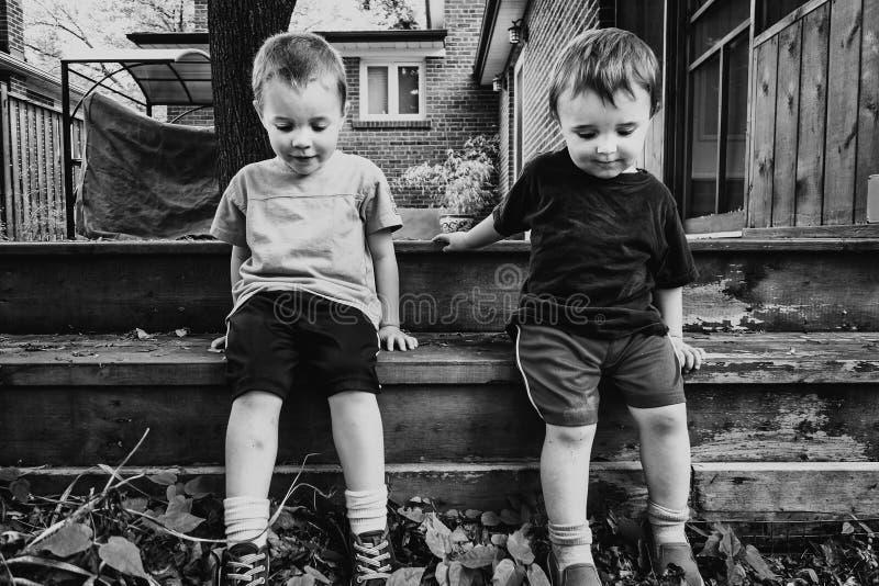 Zwei Jungen, die draußen zusammen sitzen lizenzfreies stockfoto
