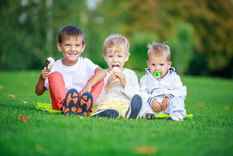 Zwei Jungen, die Eiscreme, jüngsten Bruder saugt Friedensstifter essen stockfoto