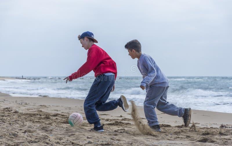 Zwei Jungen, die Fußball auf dem Strand in Korfu Griechenland spielen lizenzfreie stockfotografie
