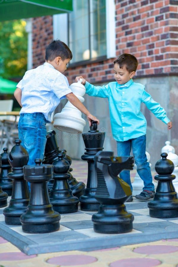 Zwei Jungen, die Schach im Freien auf einem Schachbrett mit großen Stücken an einem Sommertag spielen stockfoto
