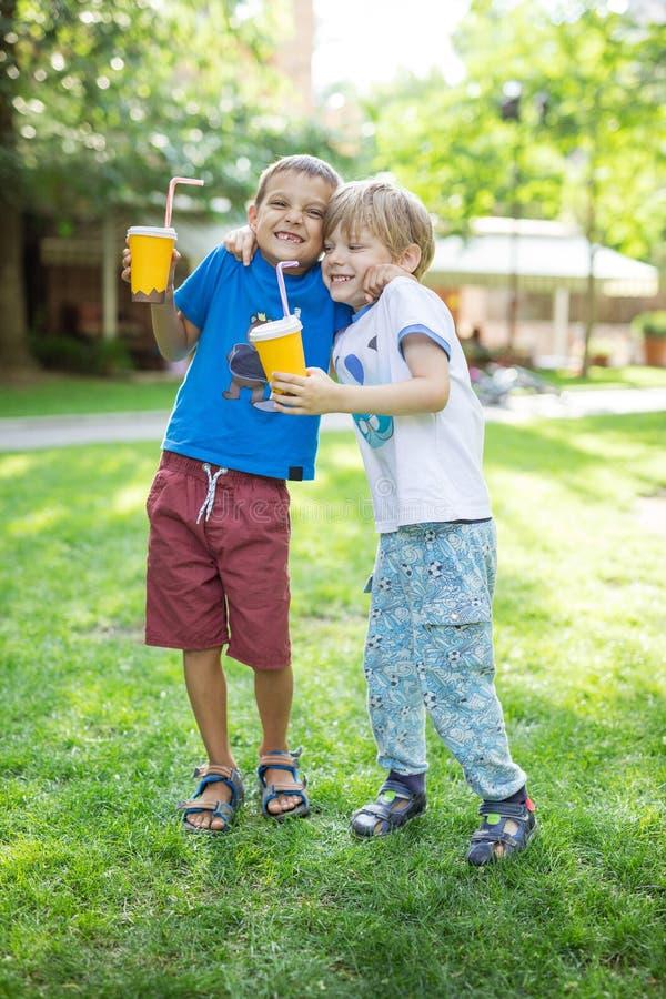 Zwei Jungen, die sich umarmen oder im Scherz beim Kakao draußen trinken kämpfen stockbild