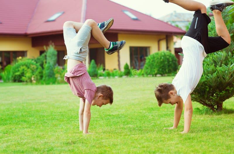 Zwei Jungen, die Spaß während des Spielens des Fußballs im Schulhof haben lizenzfreies stockfoto