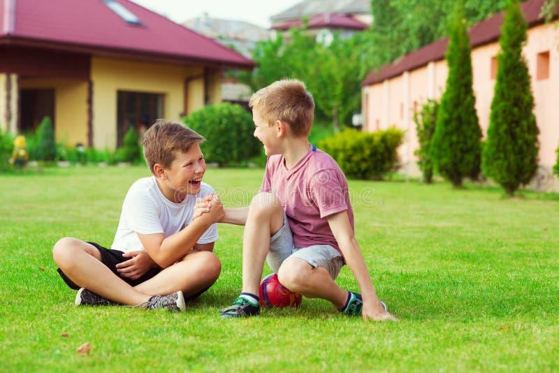 Zwei Jungen, die Spaß während des Spielens des Fußballs im Schulhof haben lizenzfreie stockfotos