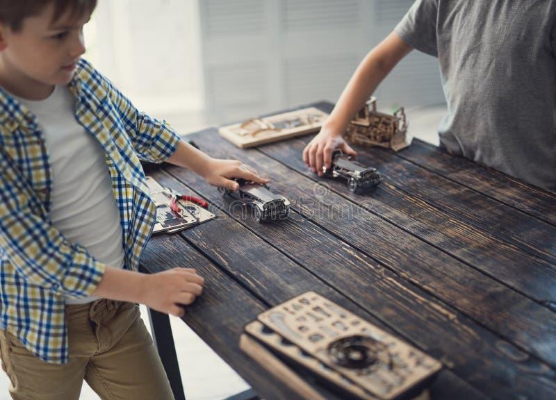 Zwei Jungen, die Spielzeugautos halten und auf dem Tisch Rennen machen stockfotos