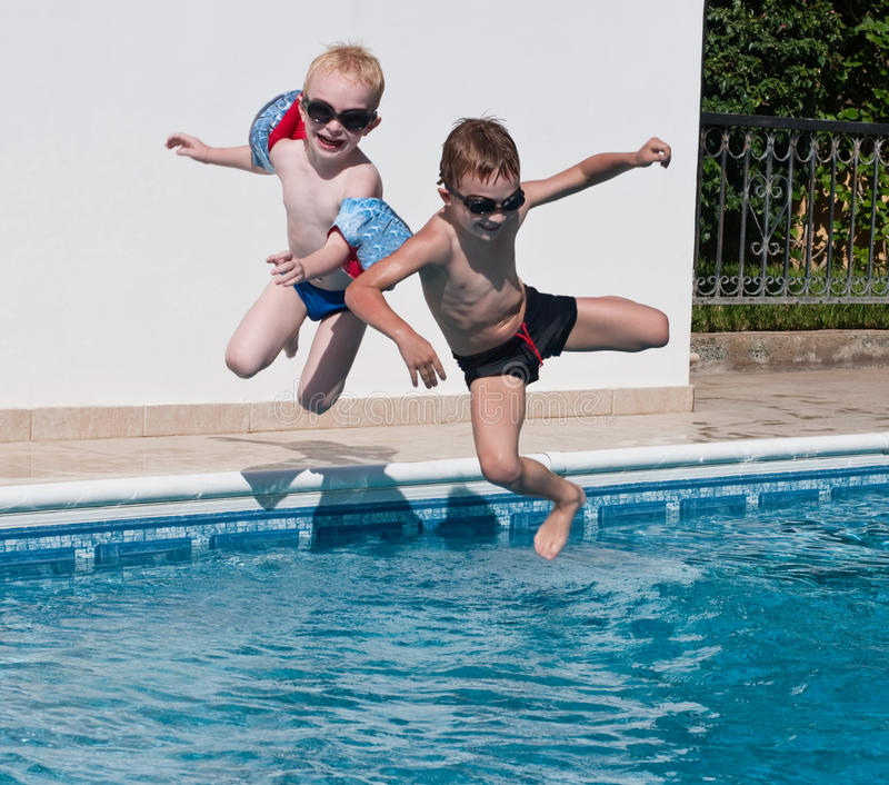 Zwei Jungen, die in Swimmingpool springen lizenzfreie stockfotos