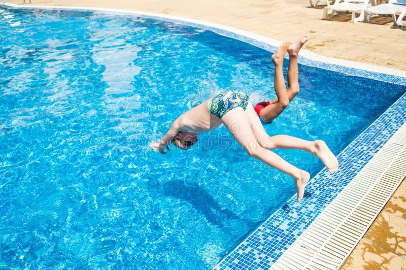 Zwei Jungen, die in Swimmingpool springen lizenzfreie stockbilder