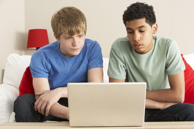 Zwei Jungen, die zu Hause Laptop verwenden stockfotografie