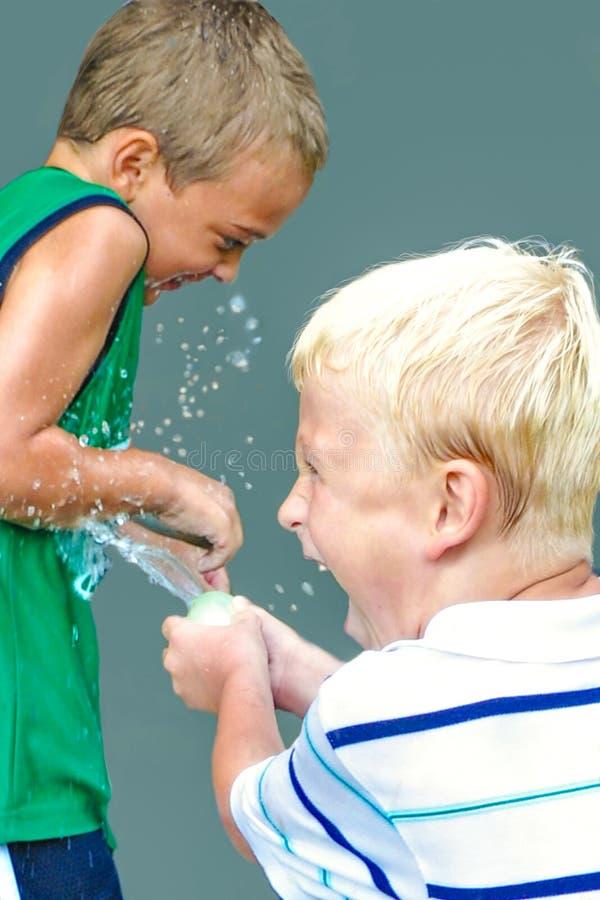 Zwei Jungen in einem Wasserbombe-Kampf stockfoto