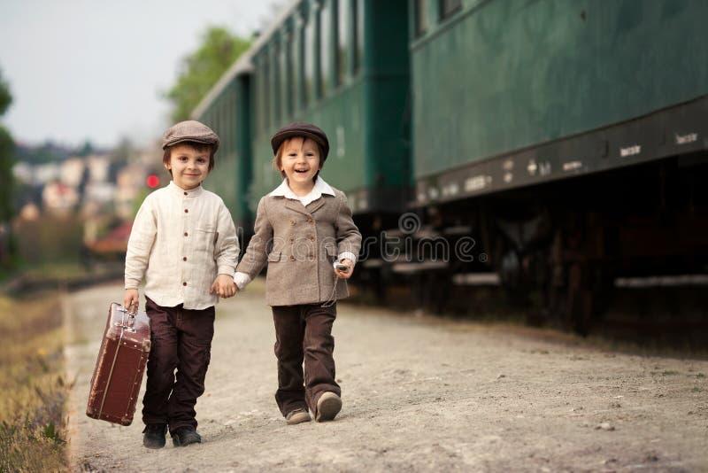 Zwei Jungen, gekleidet in der Weinlesekleidung und im Hut, mit Koffer lizenzfreie stockfotografie
