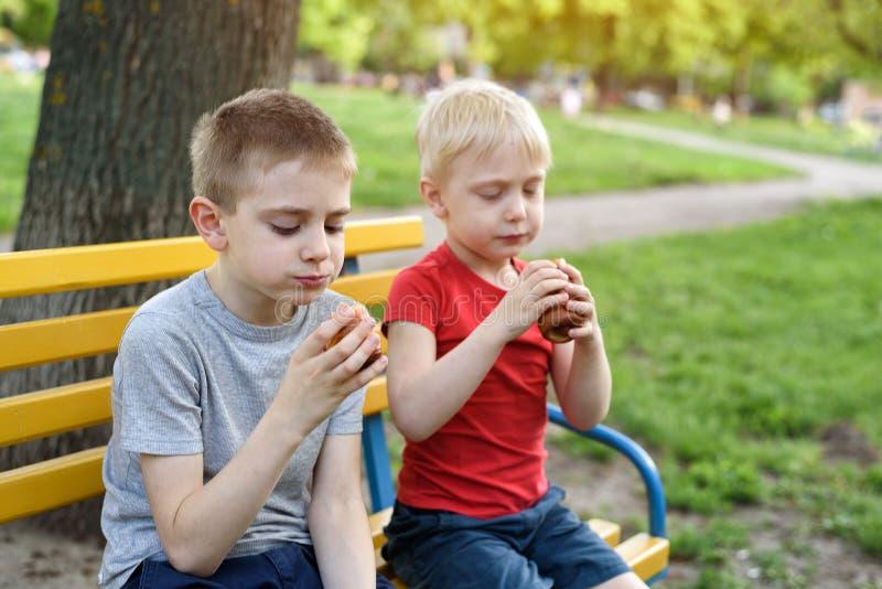 Zwei Jungen haben einen Imbiss auf einer Bank im Park und im Schwätzchen Baum auf dem Gebiet stockfotografie