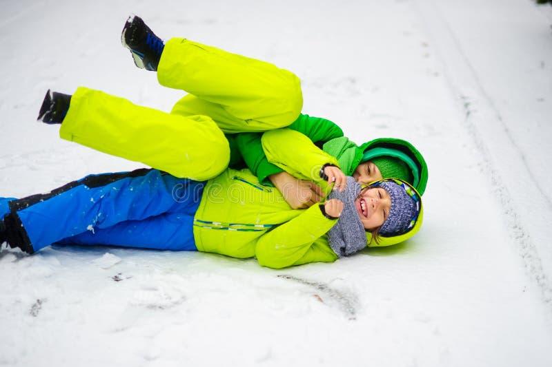 Zwei Jungen im hellen Winteroverall spielen auf Schnee stockbild