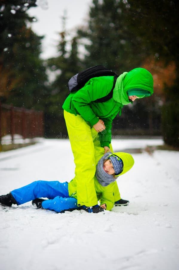 Zwei Jungen im hellen Winteroverall spielen auf Schnee lizenzfreies stockfoto