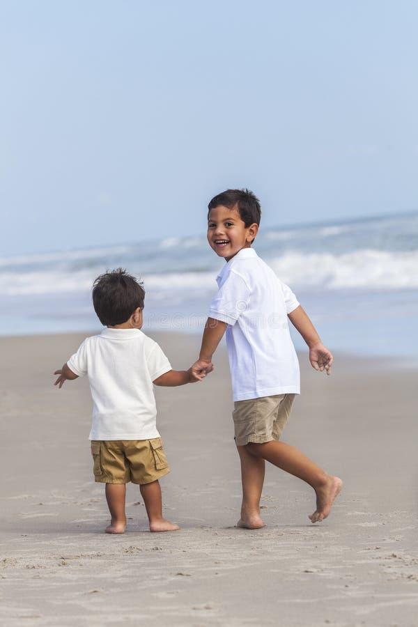 Zwei Jungen-Kinderbrüder, die auf Strand spielen stockfotografie