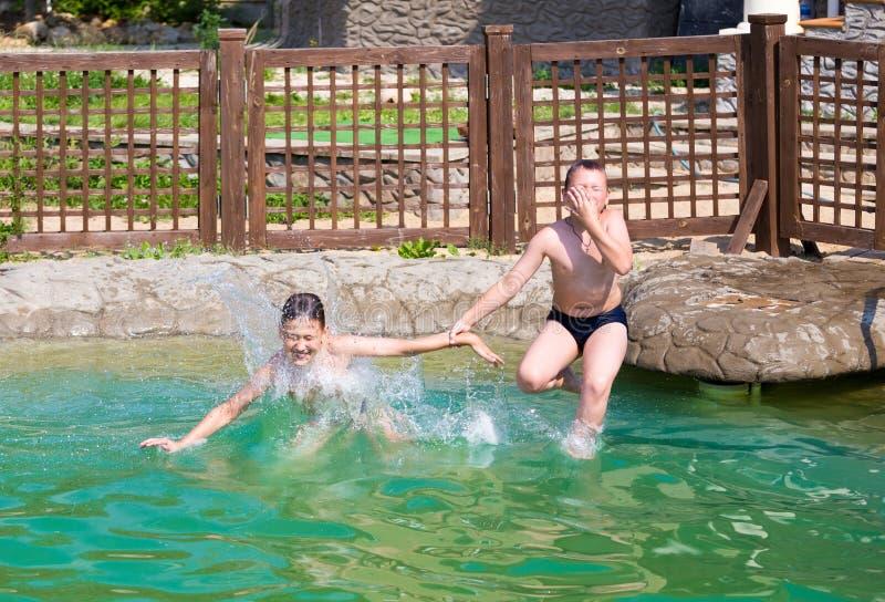 Zwei Jungen springen in das Pool stockbilder