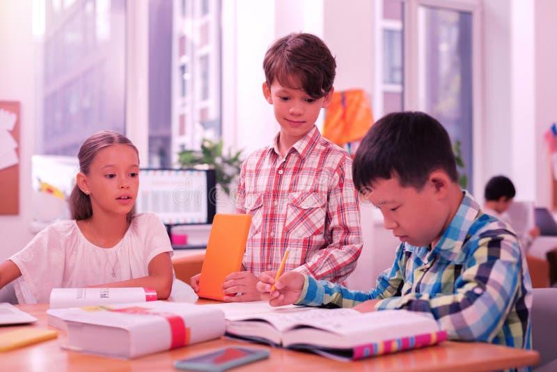 Zwei Jungen und ein Mädchen an der Lektion stockfotos