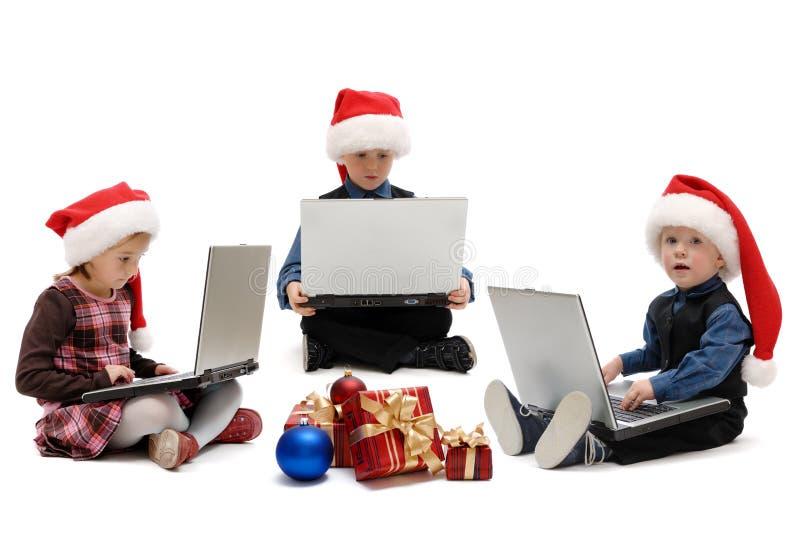Zwei Jungen und ein Mädchen in Santa Claus-Kappen mit Laptops stockfotos