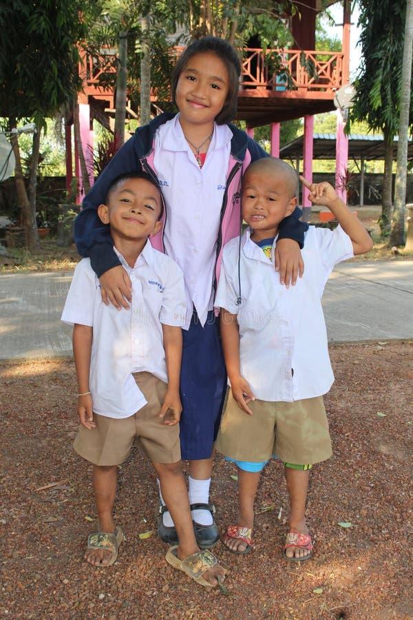 Zwei Jungen und eine Mädchenhaltung für Nehmen eine Fotografie stockfotos