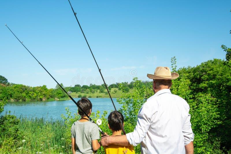 Zwei Jungen und Großväter gingen zu fischen Sie stehen auf dem Ufer des Teichs und des Blickes in den Abstand stockfotografie