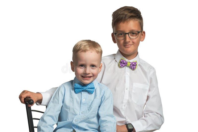 Zwei Jungenbrüder, die auf einem Stuhl im Hemd und in Schmetterling lokalisiert auf weißem Hintergrund sitzen lizenzfreies stockbild