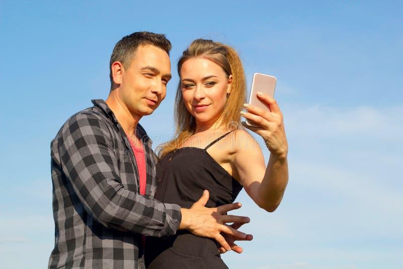Zwei junger schöner Mann und Frau in der zufälligen Kleidung, die selfi macht stockbild