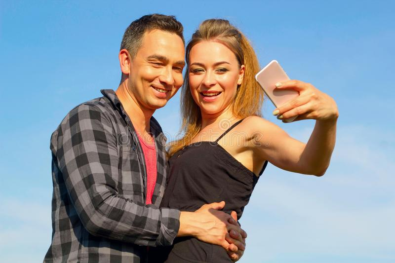 Zwei junger schöner Mann und Frau, die selfie über blauem Himmel macht stockbild