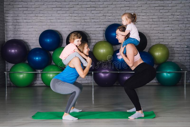 Zwei junger Sport Mutter und Babys tut Übungen zusammen in lizenzfreies stockfoto
