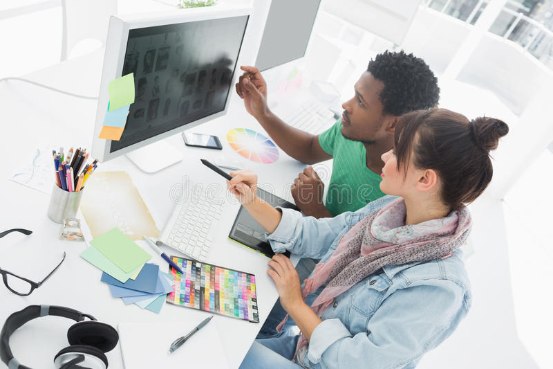 Zwei Künstler, die an Computer im Büro arbeiten stockfotografie