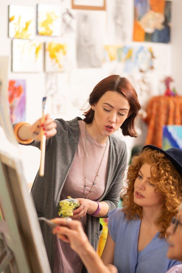 Zwei Künstler, die nahe dem gealterten Lehrer bespricht das Malen stehen lizenzfreies stockfoto