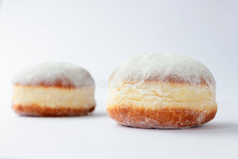 Zwei kürzlich gemachte Donuts gefüllt mit Stau und im Puderzucker bedeckt stockfotografie