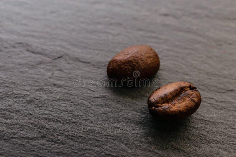 Zwei Kaffeebohnen auf einer rauen Oberfläche stockbild
