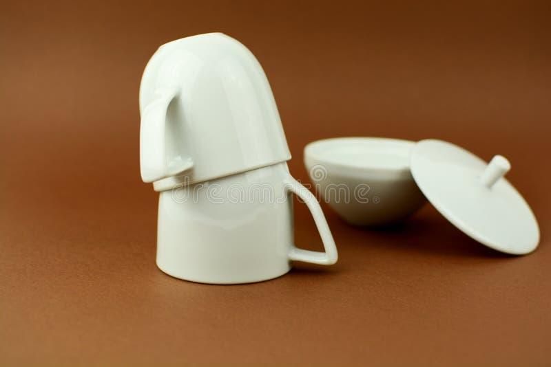Zwei Kaffeetassen, die mit Zuckerschüssel umgedreht sind, brünieren Hintergrund lizenzfreies stockbild