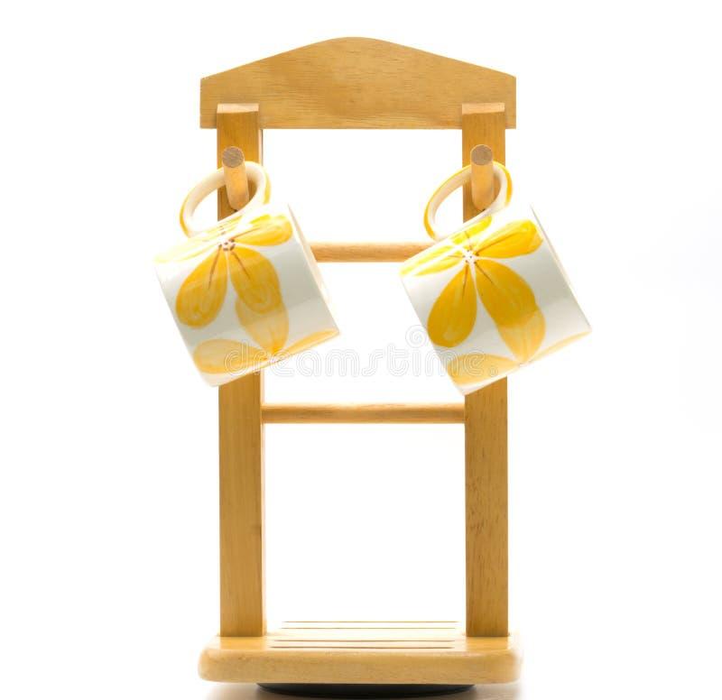 Zwei Kaffeetassen ist gemalte gelbe Blume außerhalb des Hängens am hölzernen Aufhänger mit unbedeutender Art lokalisiert stockfotografie