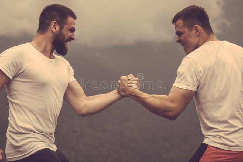 Zwei kaukasische Athleten in messenden Kräften der sportiven Abnutzung Training am im Freien lizenzfreie stockfotografie