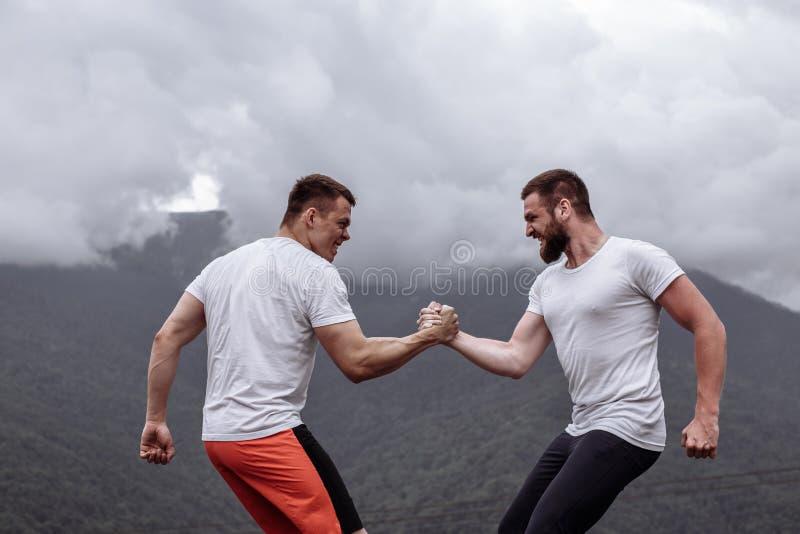 Zwei kaukasische Athleten in messenden Kräften der sportiven Abnutzung Training am im Freien lizenzfreies stockbild