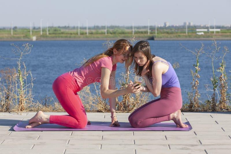 Zwei kaukasische Frauen in den Strumpfhosen und in Turnschuhen, die Yoga-Übungen auf dem Hintergrund des Flusses tun stockbild