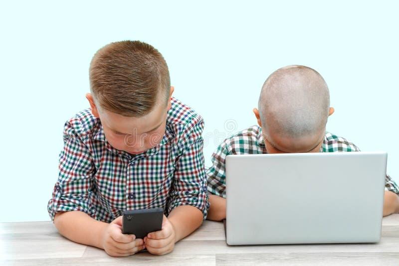 Zwei kaukasische Jungen, Brüder auf einem weißen lokalisierten Hintergrund ein spielt im Telefon, das andere im Laptop moderne Ki lizenzfreies stockbild