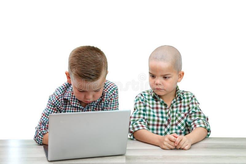 Zwei kaukasische Jungen, Brüder auf einem weißen lokalisierten Hintergrund man unterrichtet den anderen, um einen Laptop zu benut stockfotografie