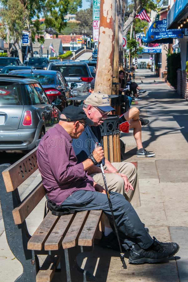 Zwei kaukasische männliche Freunde des älteren Bürgers auf einer Bank im Gewerbegebiet von Balboa-Insel stockbild