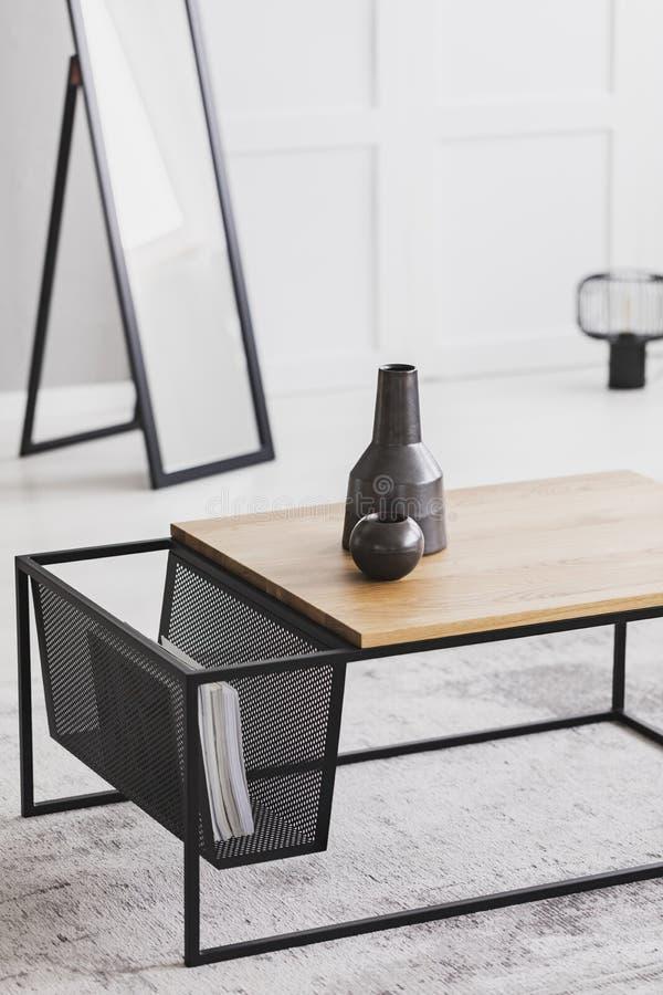 Zwei keramische Vasen in den verschiedenen Größen, die auf modernem Couchtisch im hellen Raum stehen lizenzfreie stockbilder