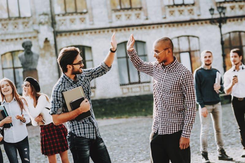 Zwei Kerle greet Hohe fünf Gruppe junge Leute stockbilder