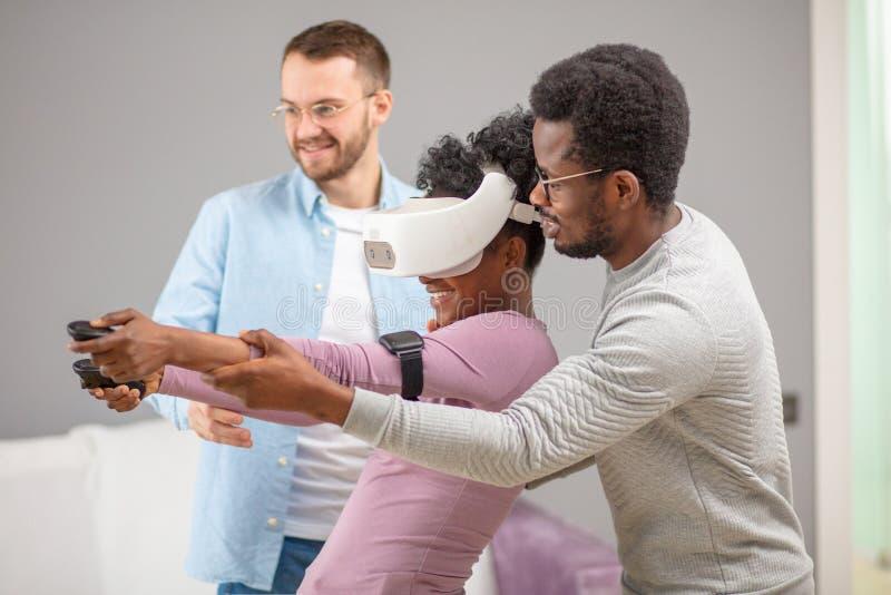 Zwei Kerle helfen der afrikanischen Frau, die zum ersten Mal auf Gl?sern der virtuellen Realit?t versucht stockbilder