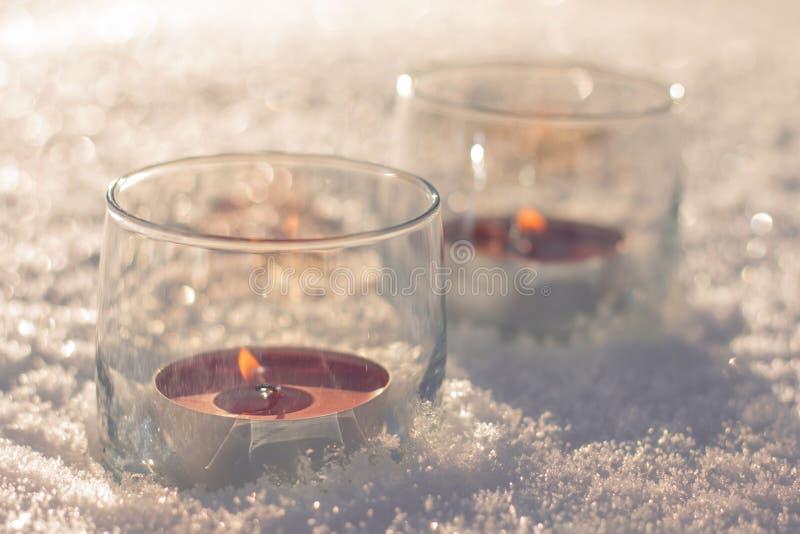 Zwei Kerzen in den Gläsern auf dem Schnee stockfoto