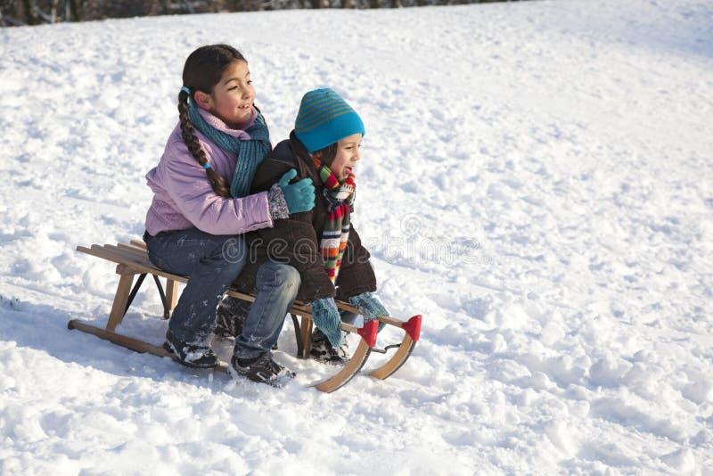 Zwei Kinder auf einem Schlitten, der Spaß hat lizenzfreie stockfotos