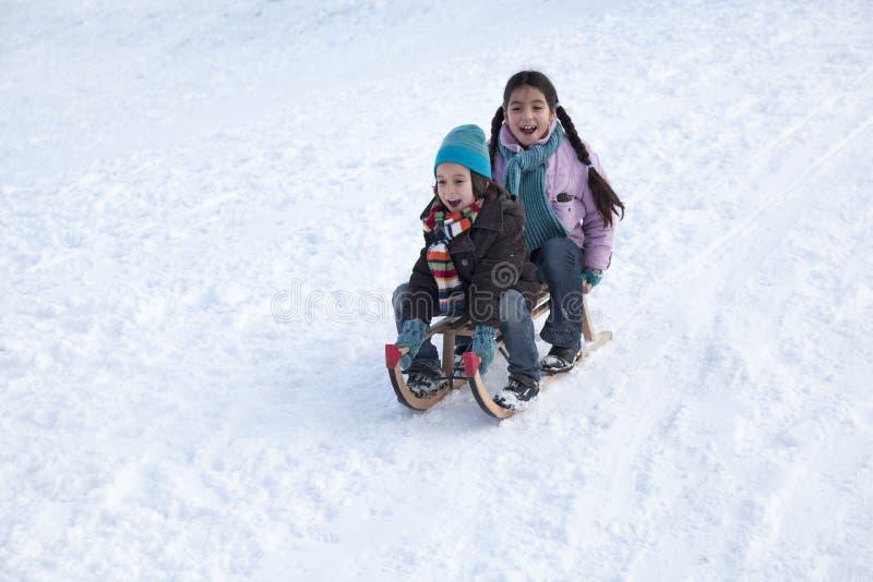 Zwei Kinder auf einem Schlitten, der Spaß hat lizenzfreies stockbild