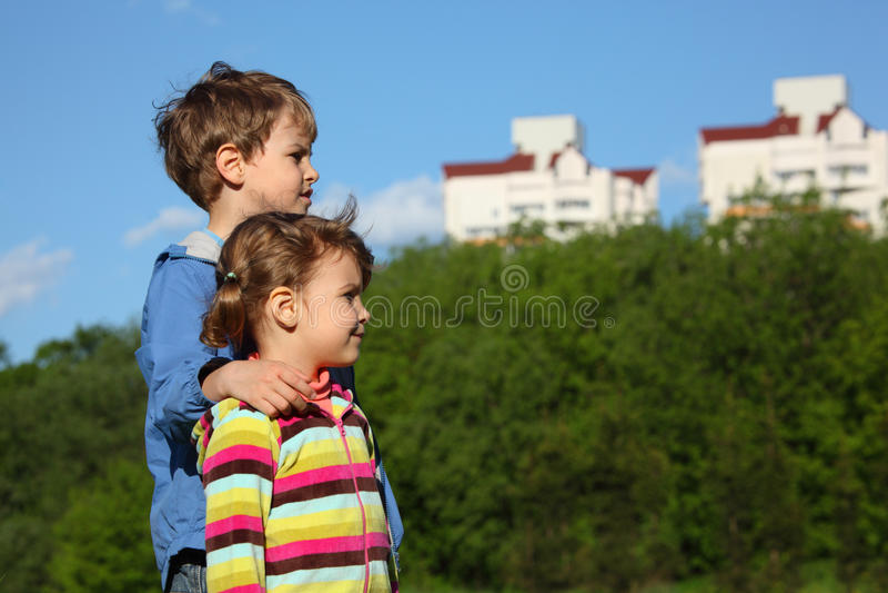 Zwei Kinder, Bäume und Häuser lizenzfreie stockfotografie