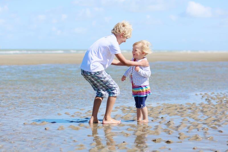 Zwei Kinder, Bruder und Schwester, spielend auf dem Strand lizenzfreie stockfotos